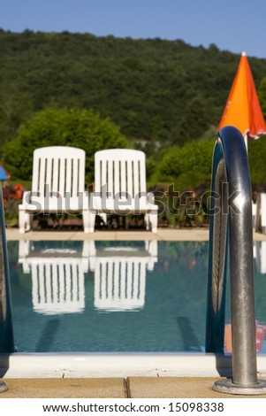 Two white sunloungers reflected in a blue swimming pool, next to an orange umbrella.  The focus is on the metal handrail in the foreground.