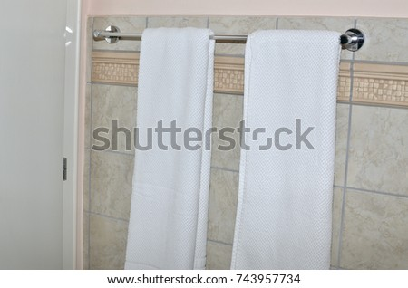 Two white towels on a towel holder in the bathroom