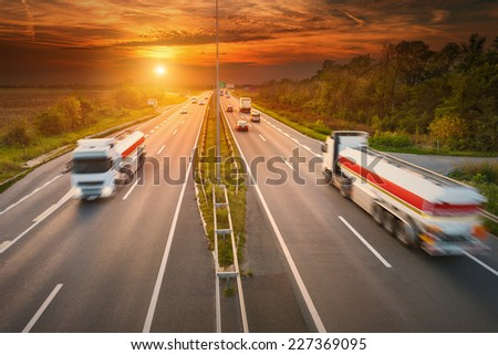 Two white trucks - cisterns in motion blur on the highway at sunset #227369095