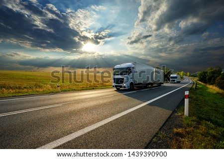 Two white trucks driving on the asphalt road in rural landscape at sunset with dramatic clouds