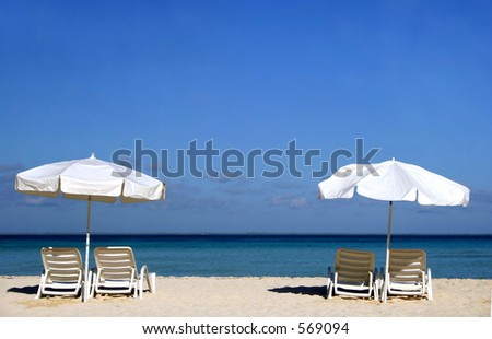 Two white umbrellas with sun loungers on a tropical beach - stock photo