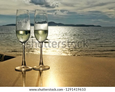 two white wine glasses with romantic sea sunset scene, island, cloud blue sky background and reflection of sunlight on water and table, evening time nobody, image for special valentine day concept