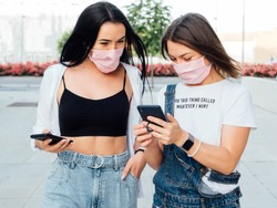 two white women in surgical masks walking down the street and looking at their mobile phones. Protection for the covid19 pandemic virus