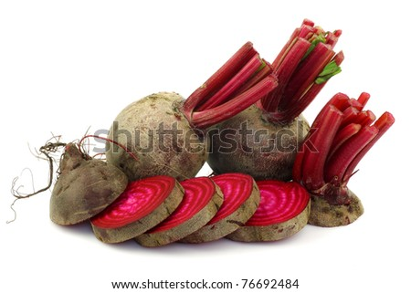 two whole beetroots and a cut one on a white background - stock photo