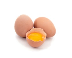 Two whole eggs and one broken isolated on a white background.