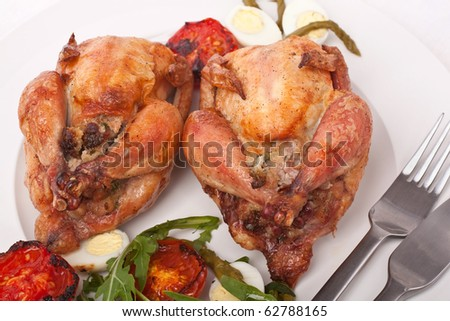 two whole grilled stuffed chickens garnished with vegetables salad on a dish