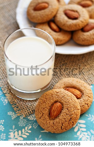 Two whole wheat almond cookies with a glass of milk and more cookies ...