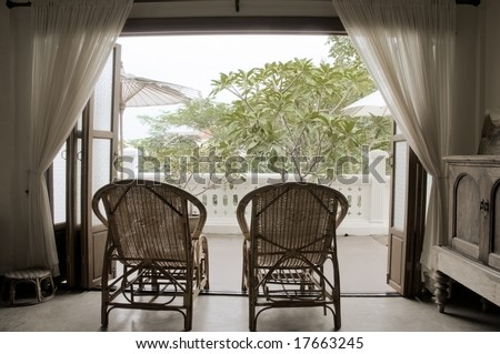 Two wicker chairs facing onto a balcony