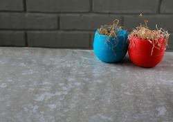 Two wilting flowers in colorful flower pots on a gray table . Dried plants in small pots against a gray brick wall. Close-up.