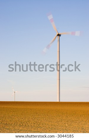 Two wind-turbines on a field at sunset. With long exposure time for motion blurred propellers of the wind-turbines.