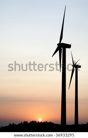 two windmills at sunrise with sun