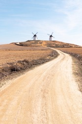 two windmills in the countryside with dirt road and straw blue sky, don quixote fields in castilla la mancha in spain europe