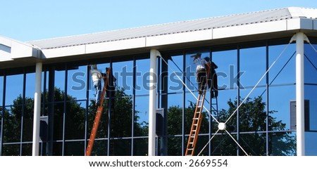 Two window cleaners at work on office building