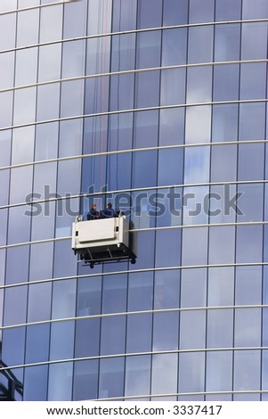 Two window cleaners in a gondola cleaning the windows of a corporate office skyscraper.