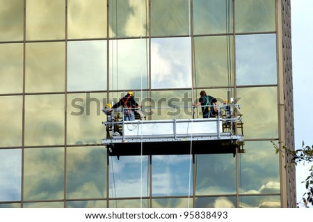 Two window washers clean exterior of building in Hancock, Michigan.  The two are suspended on roped scaffolding.