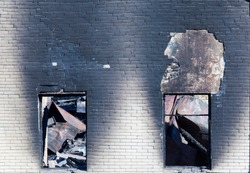two windows and part of the wall of the brick building after the fire, closeup at the site of the disaster
