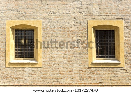 Two windows with railings and yellow stone jambs on brick medieval wall Photo stock ©