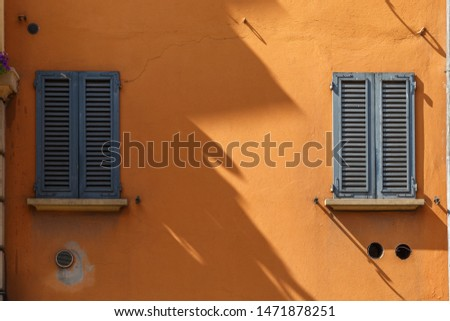 Two windows with wooden shutters on an orange house: one sunlit, the other in shadow, divided by a jagged line. Long shadows. In Bologna, Italy. Splitting concept.