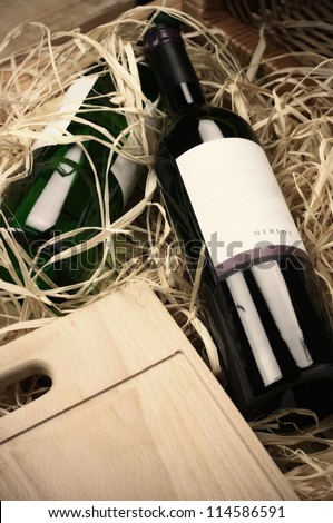 Two wine bottles lying in wooden box with straw.