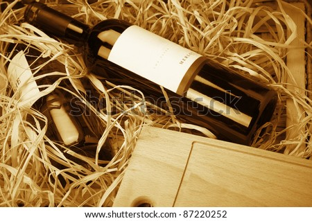 Two wine bottles lying in wooden box with straw. Monochrome toned image. Stock photo ©