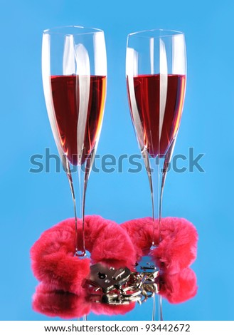 Two wine glasses and pink furry handcuffs conceptual still life isolated on blue background