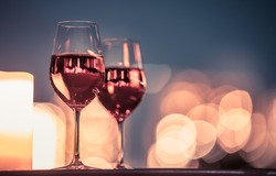 Two wine glasses in a nighttime candle light dinner, fine dinning setting.