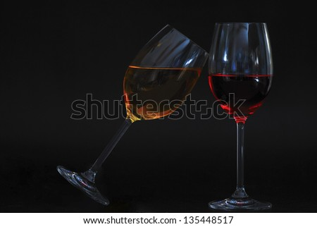 two wine glasses oblique one with yellow liquid