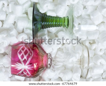 Two wine glasses, red and green, in packing peanuts