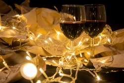 two wine glasses stand in a shining yellow garland on craft paper. cozy romantic celebration