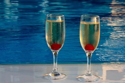 Two wine glasses, with burrowing champagne and cherries, are isolated against the background of water. Big plan. Romantic background with the ability to insert text. Holidays, holidays. Travel.