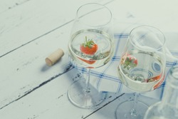 Two wine glasses with white wine and strawberry.