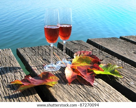 Two wineglasses and autumn leaves on a wooden jetty