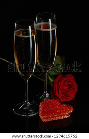 Two wineglasses of champagne, rose and red caviar on saucer in the shape of a heart standing on a black background. Valentines day #1294615762