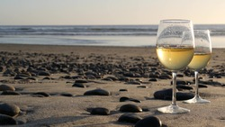 Two wineglasses on sandy ocean beach. Couple of glasses and pebbles, white wine for romantic date near sea water. Cozy beachfront sunset near tide waves. Seamless looped cinemagraph. California, USA.