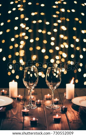 Two wineglasses on served wooden table surrounded by lit candles