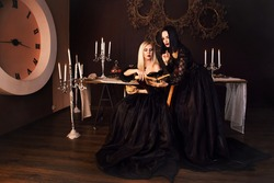 Two witches perform a magic ritual love spell. Magic. The sorceress is a sorceress who reads the future in a magic book. fantasy beautiful girls in the image of a witch in a dark gothic room.