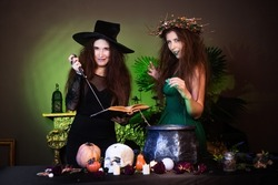 Two witches with a book and a dagger are preparing a potion in a cauldron standing in a dark room. Celebrating halloween.