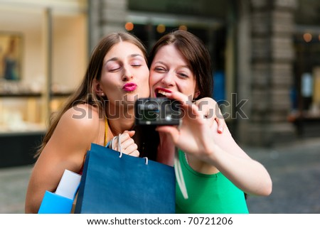 Two woman being friends shopping downtown with colourful shopping bags and taking a picture from themselves