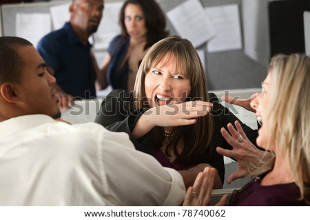 Two woman employees quarreling among other coworkers