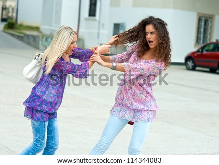 two woman fight each other in the street and pulling hair