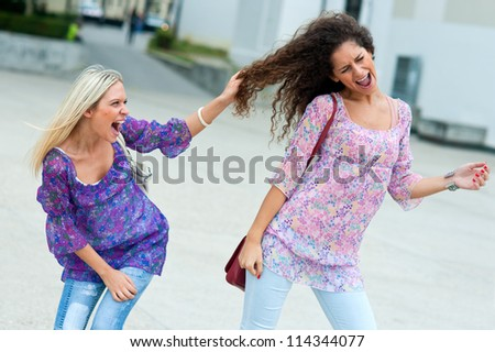 two woman fight in the street and pulling hair