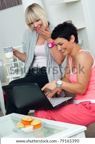 two woman friends with laptop sitting on sofa at home