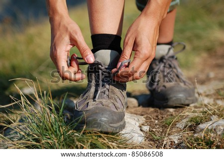 Two Woman Hands Lacing up Trekking Shoes
