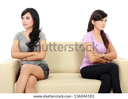 two woman hates each other. sitting on the couch