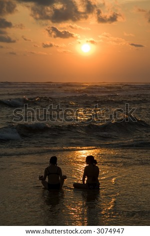 Two woman in a Lotus position as the sun sets over the pacific