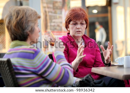 Two woman in cafe, selective focus on gesturing woman - stock photo