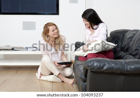 Two woman in their sitting room chatting and having fun on an electronic tablet - stock photo
