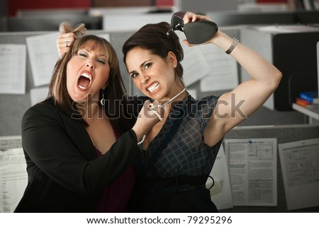 Two woman office workers quarreling in cubicle