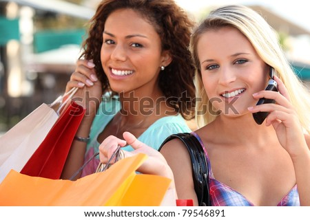 Two woman on mobile phones holding shopping bags