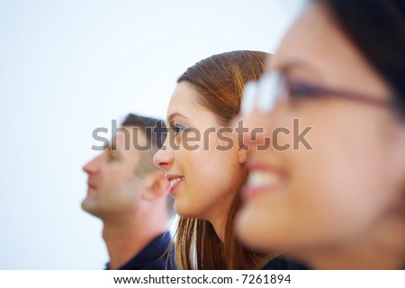 two woman one male  profiles  view in a row smiling in  business interior